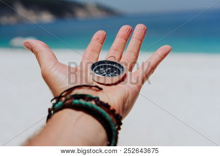 Outstretched Hand Holding Black Metal Compass Against White Sandy Beach And Blue Sea. Find Your Way