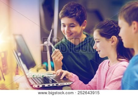 renewable energy, children, technology, science and people concept - group of happy kids or friends with laptop computer and wind turbine model at school