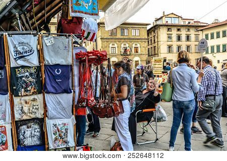 Florence, Italy - September 19 2016: A Local Street Vendor Selling Gifts And Souvenirs Gestures To A