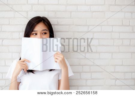 Beautiful Portrait Young Asian Woman Happy Hiding Behind Open The Book With Cement Or Concrete Backg