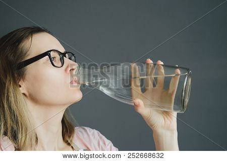 Girl In Glasses Drinks Water From Glass Bottle, Close-up Portrait Of White Caucasian Woman, Stock Ph