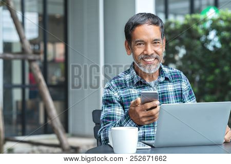 Smiling Happy Mature Asian Man With White Stylish Short Beard Using Smartphone Gadget Serving Intern
