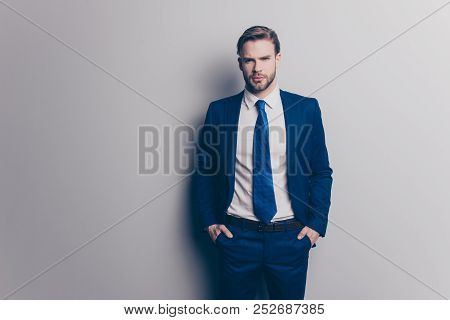 Portrait Of Stunning, Attractive, Sexy, Brutal Man In Blue Suit With Tie With Stubble, Holding Two H