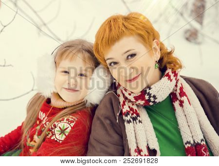 mom and daughter, both red hair walking in costumes of flowers traditional elves Santa's helpers in the winter forest under the snow with a chest of gifts and giant candy, new year poster