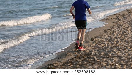 Runner While Training In The Morning Lends On The Shore Of The Beach By The Sea