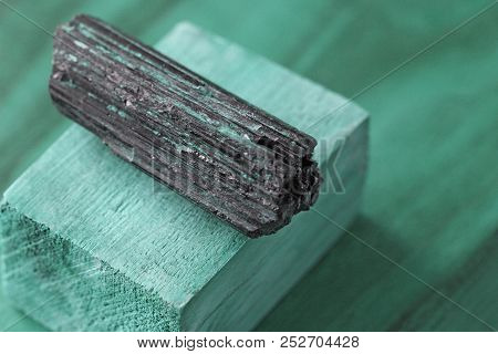 Black Tourmaline Stone On A Background Of Natural Wood American Black Walnut. Mineral Collection Sto