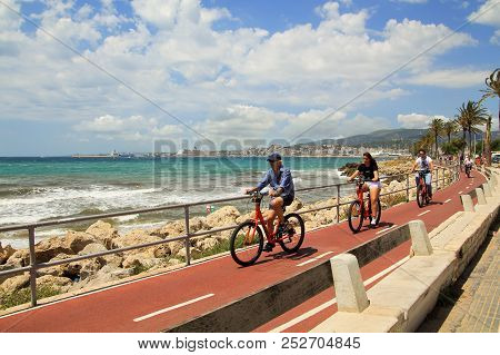 Majorca, Spain - June 13, 2018: Cyclists Riding On The Seafront Of The Palma De Mallorca.