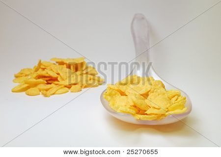 Transparent plastic spoon with cornflakes and pile of cornflakes