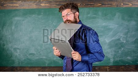 Thirst of knowledge. Teacher bearded man bites modern laptop chalkboard background. Hipster teacher wear eyeglasses and necktie bites laptop. Man hungry for knowledge. He needs new information poster