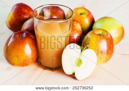 Glass Of Fresh Apple Juice And Half Apple Near Autumn Apples.