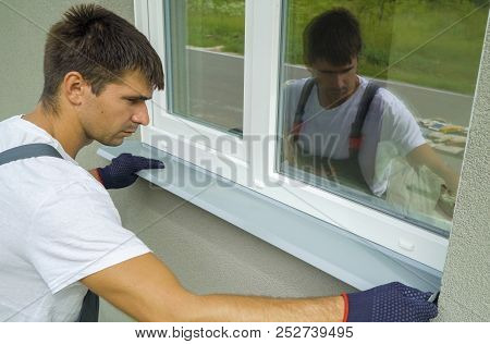 Man Worker In Protective Gloves Measuring External Frame And Pvc Window Metal Sill Size. Builder Che