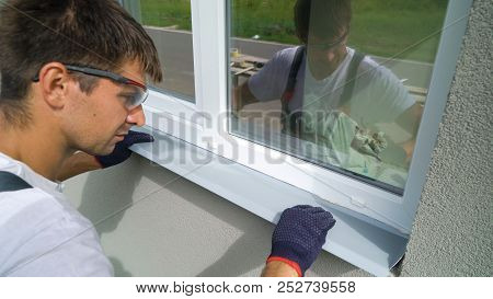 Man worker in safety glasses and protective gloves installing metal sill on external PVC window frame. Window sill installation process. Technology, exterior design, building concept poster