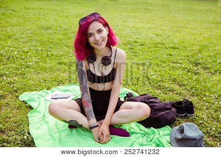 Young Informal Woman With Pink Hair And Tattoos Sitting On Plaid In Green Park Squinting Eyes From H