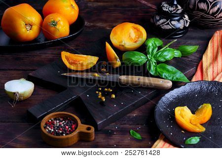 Yellow Tomatoes On A Cutting Board With Basil