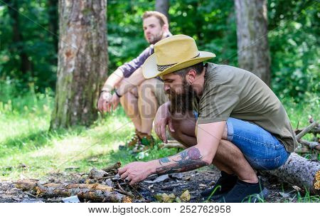 Men on vacation. Masculinity concept. Ultimate guide to bonfires. How to build bonfire outdoors. Arrange the woods twigs or wood sticks. Man brutal bearded hipster prepares bonfire in forest poster