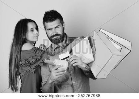 Guy With Beard And Girl With Sly Faces Do Shopping. Couple In Love Holds Shopping Bags On Pink Backg