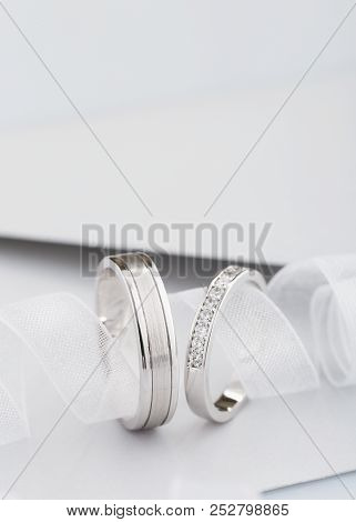 Two Silver Wedding Rings With Diamonds On Gray Background. White Gold Rings With Gems. Wedding Invit