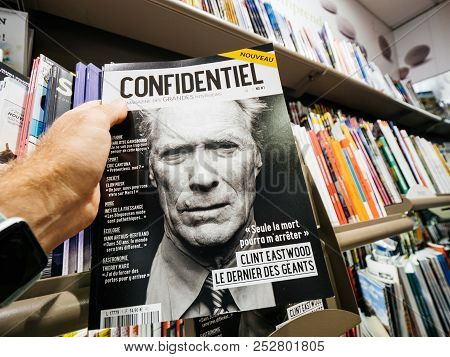 Paris, France - Jul 16, 2018: Man Buying  Confidential Magazine Featuring Clint Eastwood