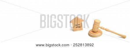 Wooden House And Hammer Of The Judge On A White Background. Trial Property. The Court Decision On Th