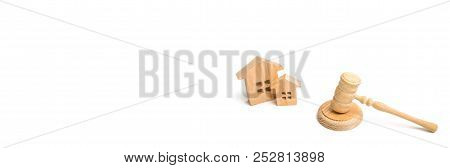 Two Wooden Houses And A Hammer Of The Judge On A White Background. Court Cases On Property And Real