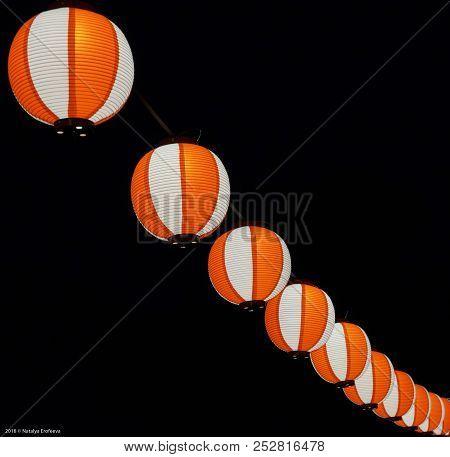 Paper Red-white Asian Japanese Chinese Lanterns Chochin Akachochin Shines On Dark Sky. A Garland Of