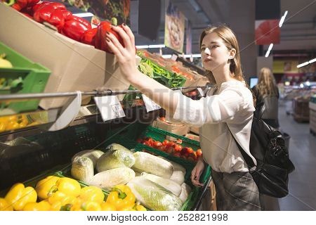 Stylish Woman Chooses Vegetables On The Supermarket Shelves. Girl Buys The Pepper In The Vegetable D