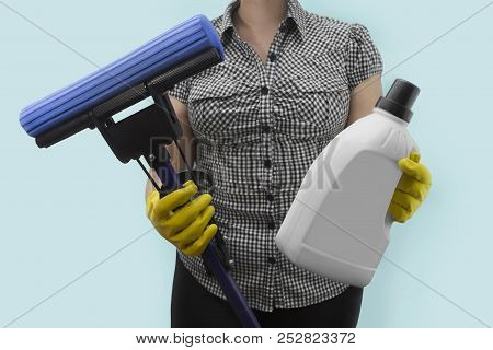 A Young Housewife Holding A Mop And A Bottle Of Liquid Detergent.