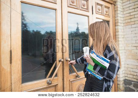 A Girl Student In Casual Clothing, Books And Notebooks In His Hands Opens The Door To The University