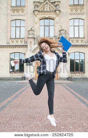 Joyful Student Girl Jumping With Books And A Cup Of Coffee In The Hands Of The University Building.
