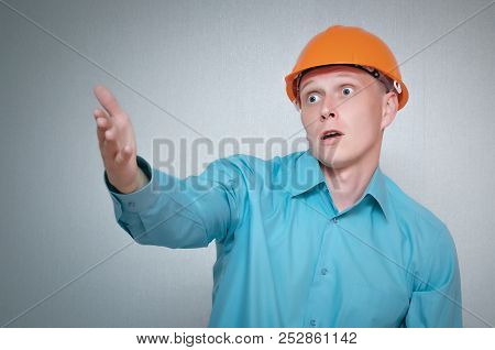 Confused And Discouraged Builder Worker Man Isolated On Gray Background.