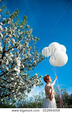 Red haired girl holding massive helium balloons her face turned at the sun in a blossoming garden poster