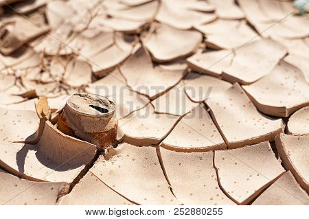 Old Rusty Can Of Soda On Dry Cracked Soil. Drought, Climate Changes Concept.