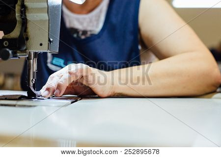 Cropped View Of The Close Up Of The Hands Of A Woman Sewing With The Machine A Piece Of Leather To B