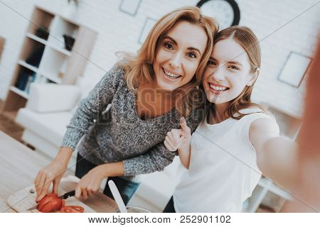 Smiling Mother And Daughter Taking Selfie In Kitchen. Relationship In Family. Holiday At Home. Healt