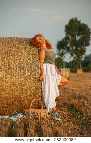 Red-haired woman posing on the field near a haystack