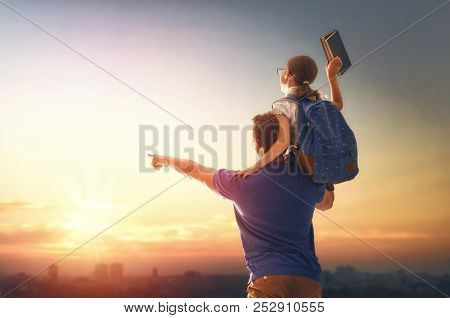 Parent and pupil of primary school on sunset background. Man and girl with backpack behind the back. Beginning of lessons. First day of fall.