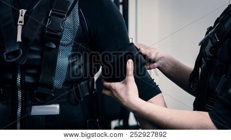 Female coach helping man with putting electro muscular stimulation suit on poster