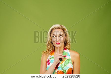 Portrait Of A Grumpy Blonde Woman Looking Down, Isolated On Green Studio Background