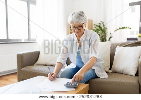 finances, savings, annuity insurance and people concept - senior woman with calculator and bills counting dollar money at home poster