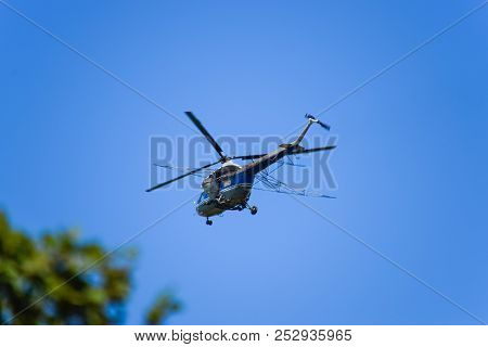 A Helicopter Of Agricultural Aviation Is Flying In The Blue Sky. Helicopter For Spraying Fertilizers