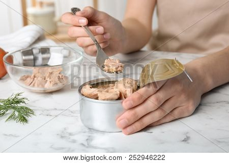 Woman With Tin Can Of Conserved Tuna At Table