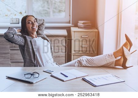 Pretty Business Lady Smiling And Sitting In Modern Office With Legs On Table At Working Place. Relax