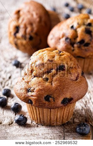 Delicious Homemade Blueberry Muffins On A Rustic Wooden Table.