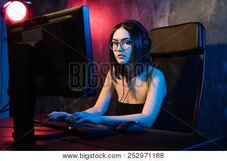 Beautiful Young Girl Wearing Glasses And Gaming Headset Plays Online Game On Gaming Pc In Dark Area.
