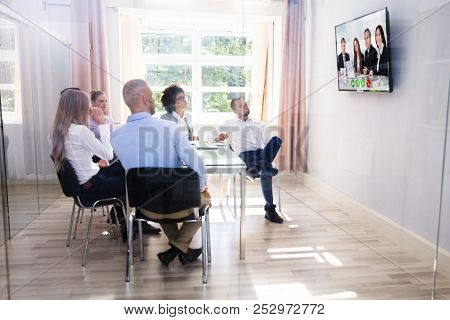 Group Of Diverse Businesspeople Looking At Television While Video Conferencing In Boardroom