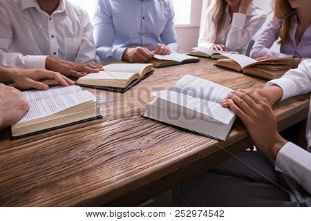 Group Of People Reading Bible On Wooden Desk