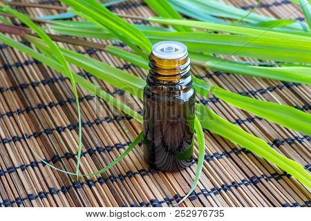A Bottle Of Essential Oil With Fresh Lemon Grass On A Table