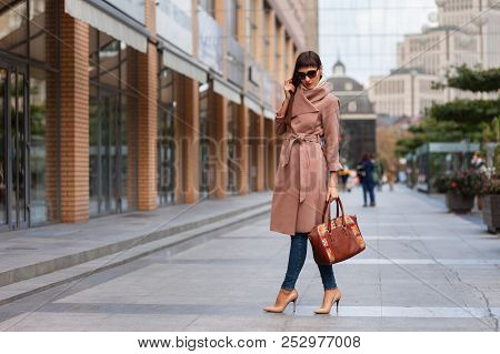 Beautiful Brunette Young Woman In Nice Brown Beige Coat, Jeans And Sunglasses. High Heels Shoes. Spi