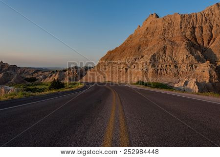 Low Angle Of Road Stripes Through Badlands Rock Formation