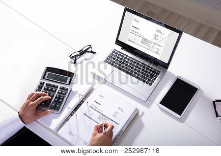 High Angle View Of Businessperson Calculating Invoice With Laptop On Desk